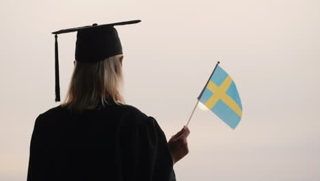 Rear-View-Of-A-Graduate-With-The-Flag-Of-Sweden-In-Hand-Study-In-Norway