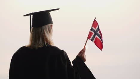 Rear-View-Of-A-Graduate-With-The-Flag-Of-Norway-In-Hand-Study-In-Norway