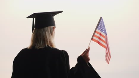 Graduate-In-Mantle-With-Usa-Flag-In-Hand-Meets-The-Dawn