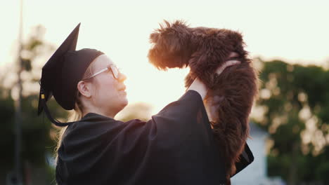 A-Woman-In-A-Graduate-Costume-Holds-A-Cute-Puppy-In-Her-Arms-College-Graduation-Gift