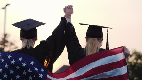 Two-Women-College-Graduates-Raise-Their-Hands-Up-On-The-Shoulders-Of-The-Usa-Flag