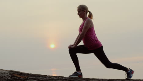 Active-Middle-Aged-Woman-Is-Training-Against-The-Backdrop-Of-The-Sea-And-The-Rising-Sun