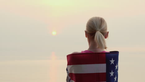 A-Woman-With-The-Flag-Of-America-On-Her-Shoulders-Looks-At-The-Sunrise-Over-The-Sea