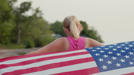 Woman-In-Sportswear-With-Usa-Flag-On-Her-Shoulders-Walks-Along-The-Seashore