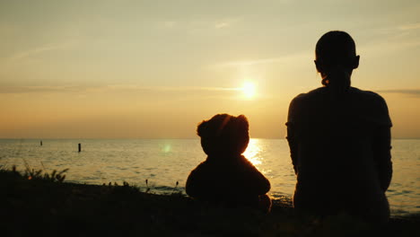 Silhouette-Of-A-Woman-And-A-Teddy-Bear-On-The-Lake-Looking-Forward-Over-The-Horizon-Where-The-Sun-Se