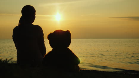 A-Lonely-Woman-With-A-Toy-Bear-Looks-At-The-Sunset-Over-The-Sea-Sadness-And-Loneliness-Concept