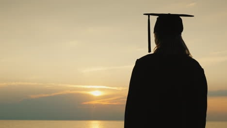 A-Bachelor-With-A-Diploma-In-Hand-And-A-Cap-Of-A-Graduate-Looks-At-The-Sunrise-Over-The-Sea