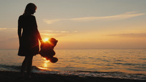 A-Woman-With-A-Teddy-Bear-In-Hand-Is-Standing-On-The-Seashore-When-The-Sun-Sets-Childhood-Dreams
