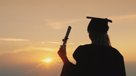 Graduate-With-A-Diploma-Looks-At-The-Sunrise-Over-The-Sea---Perspective-And-Inspiration-Concept