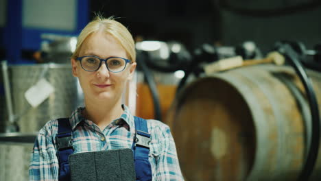 Portrait-Of-A-Woman-Worker-In-A-Winery-Wine-Barrels-In-The-Background