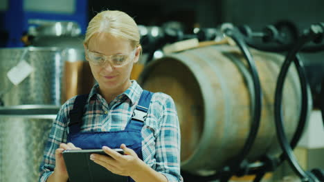 Lab-Technician-With-Protective-Glasses-Works-With-A-Tablet-In-The-Workshop-On-The-Background-Of-Wine
