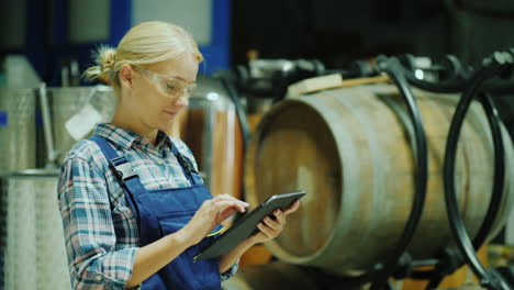 A-Woman-Uses-A-Tablet-In-A-Winery-Workshop-In-The-Background-Are-Wooden-Barrels