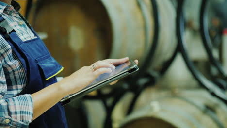 Hands-Of-A-Worker-With-A-Tablet-On-A-Background-Of-Wine-Barrels-Works-In-The-Winery