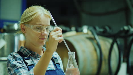 Female-Researcher-Working-With-Product-Samples-In-A-Flask-Against-The-Background-Of-Wooden-Barrels-O