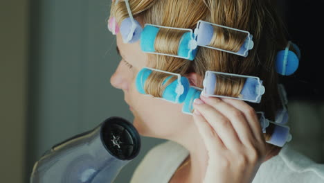 Woman-With-Curlers-On-Her-Head-Dries-Hair-With-A-Hairdryer