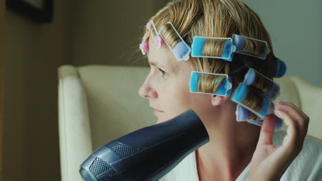 A-Young-Woman-Dries-Hair-With-A-Hairdryer-Curlers-On-Her-Head-To-Give-Shape-To-Her-Hairstyle