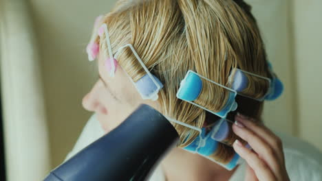 Woman-With-Curlers-On-Her-Head-Dries-Hair-With-A-Hairdryer-Close-Up-Shot