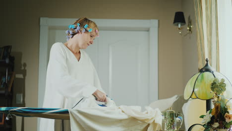 Woman-In-A-Bathrobe-With-Curlers-On-Her-Head-Ironing-Clothes
