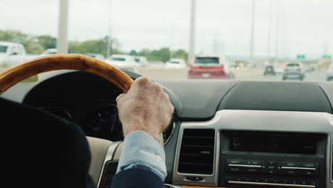 Hands-Of-A-Business-Man-On-The-Steering-Wheel-Of-A-Luxury-Car