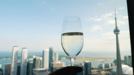 Hand-With-A-Glass-Of-Wine-Against-The-Background-Of-The-Window-Where-The-Famous-Cn-Tower-Of-Toronto-