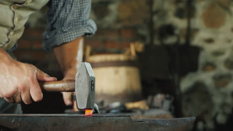 A-Blacksmith-With-Forceps-Holds-A-Red-Hot-Billet-Above-The-Anvil-Striking-It-With-A-Hammer-Tradition