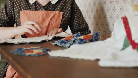A-Woman-In-An-Antique-Dress-From-The-Time-Of-The-Development-Of-America-Is-Engaged-In-Needlework