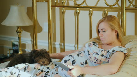 A-Pregnant-Woman-Uses-A-Tablet-In-Her-Bedroom-Her-Dog-Lies-Beside-Her