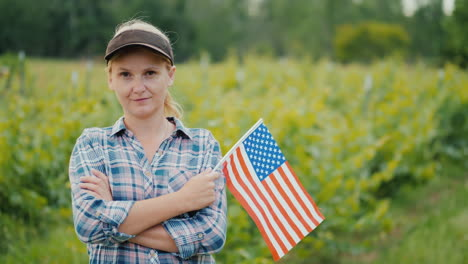 Woman-Farmer-With-Usa-Flag-Looking-At-The-Camera-Portrait-Of-An-American-Farmer