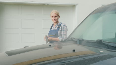A-Woman-Washing-My-Car-In-The-Backyard-Of-Her-House-On-The-Background-Of-The-Doors-To-The-Garage