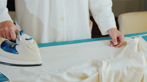 Female-Hands-With-An-Iron-Ironing-At-A-White-Elegant-Shirt