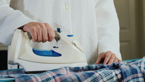 Woman-s-Hands-Ironing-A-Plaid-Shirt