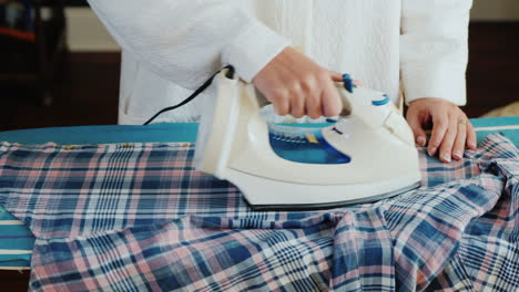 Young-Attractive-Woman-Ironing-Clothes-At-Home