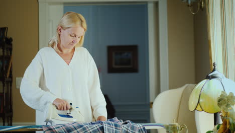 Middle-Aged-Woman-Ironing-Clothes-On-An-Ironing-Board