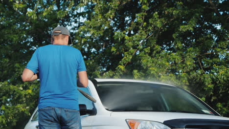 A-Man-Washes-His-Car-In-The-Backyard-Rear-View