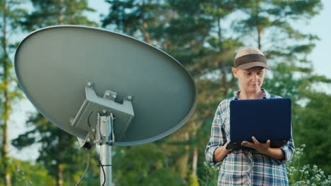 Technician-Sets-Up-A-Terrestrial-Satellite-Dish-Uses-A-Laptop