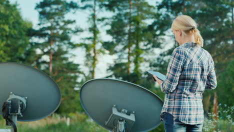 Woman-Tunes-Satellite-Dishes-Outdoors-Uses-Tablet