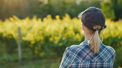 Rear-View-Of-A-Woman-Farmer-Looking-At-Her-Garden