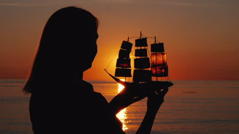 Silhouette-Of-A-Woman-With-A-Sailboat-In-Her-Hands-The-Setting-Sun-Shines-Through-The-Sails-Inspirat
