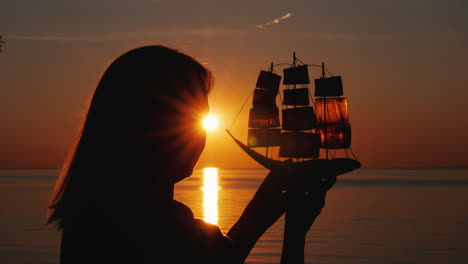 A-Woman-Stands-By-The-Sea-At-Sunset-Holds-In-Her-Hands-A-Model-Of-A-Sailing-Ship-Hope-And-Travel-Con