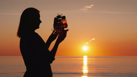 A-Woman-With-A-Boat-In-Her-Hands-Stands-By-The-Sea-Where-The-Sun-Sets-Creativity-And-Inspiration-Con