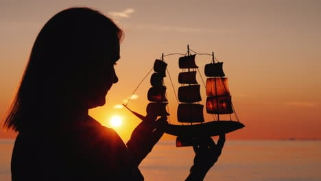 Profile-Of-A-Woman-With-A-Toy-Sailboat-Against-The-Setting-Sun