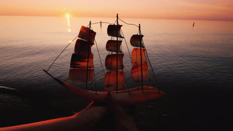 Hands-Of-A-Young-Couple-Raise-Up-A-Model-Of-A-Sailing-Ship-On-The-Background-Of-The-Sea-And-Sunset-C