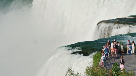 Tourists-On-The-Observation-Deck-Stand-Against-The-Background-Of-A-Wall-From-The-Water-Of-Niagara-Fa