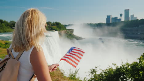 Traveling-In-The-Usa---A-Woman-With-The-Flag-Of-America-In-Her-Hand-Admires-Niagara-Falls-One-Of-The