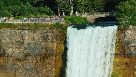 Waterfall-Veil-Of-The-Bride-And-Tourists-Strolling-Over-It-Famous-Niagara-Falls-On-The-Border-Of-Ame