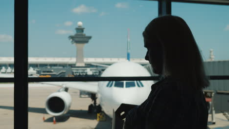Silhouette-Of-A-Woman-At-The-Window-Of-An-Airport-Terminal-Eating-Snacks-While-Waiting-For-A-Flight