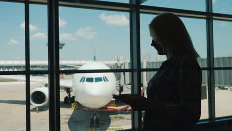 Silhouette-Of-A-Business-Woman-By-The-Window-Of-An-Airport-Terminal-Uses-A-Smartphone