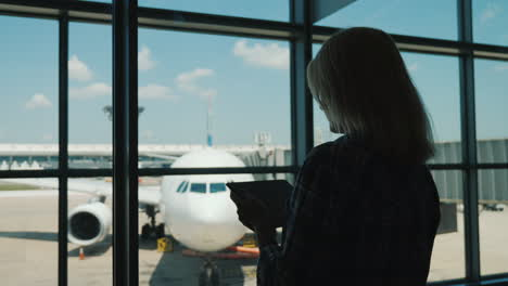 Silhouette-Of-A-Business-Woman-By-The-Window-Of-An-Airport-Terminal-Uses-A-Digital-Tablet