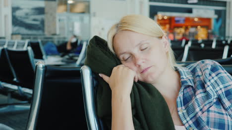 A-Young-Woman-Fell-Asleep-In-The-Airport-Terminal-Flight-Delay-Or-Cancellation-Concept