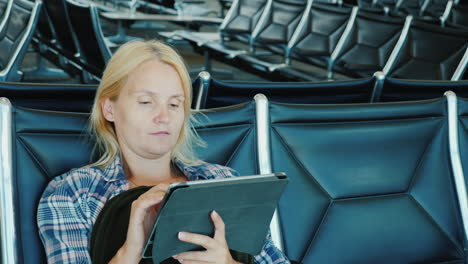 A-Woman-Uses-A-Tablet-In-An-Airport-Lounge-Leisure-Pending-Flight